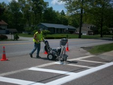 Worker painting cross walk lines