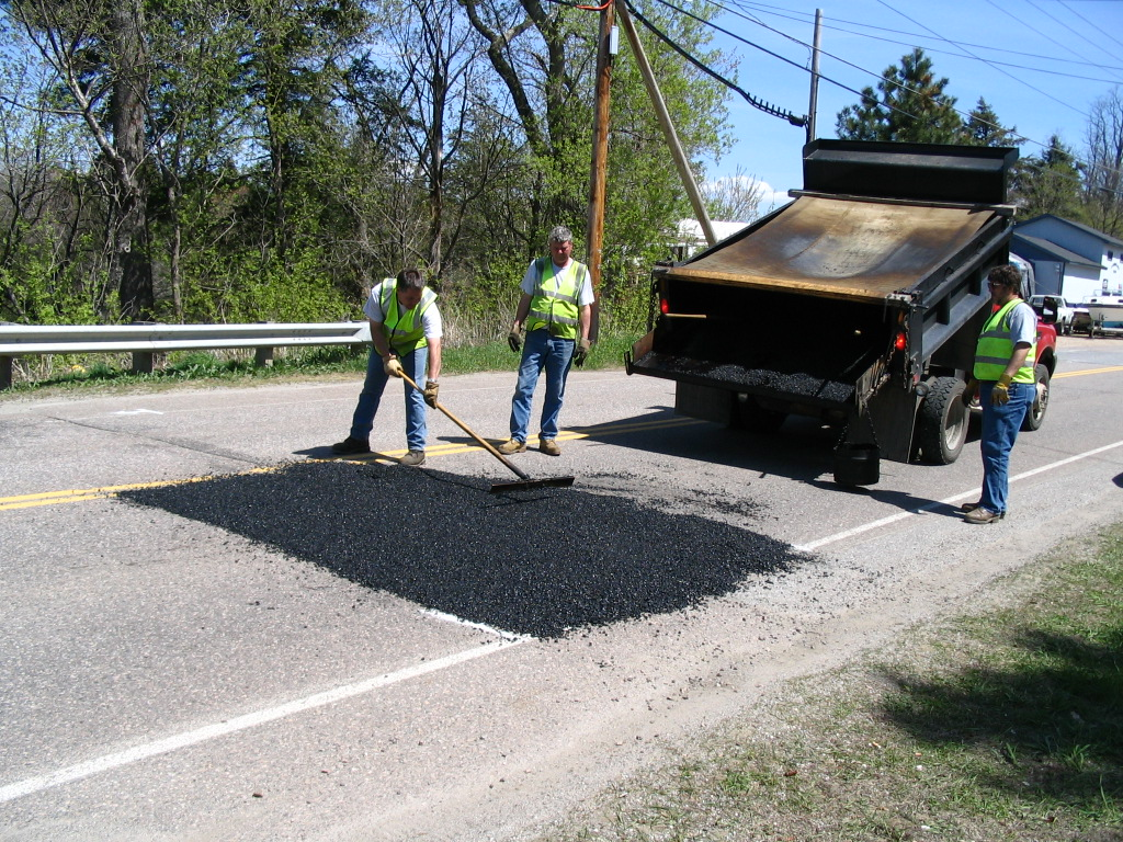 Workers smoothing out tar on road