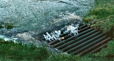 Storm water pouring into a drain