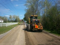 Back of Cat tractor grading a gravel road