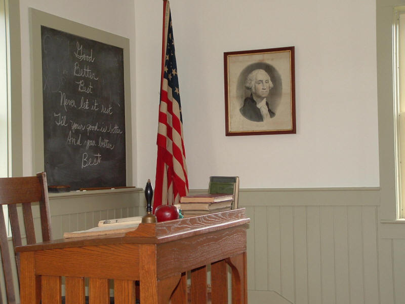 Teachers desk, flag, chalkboard
