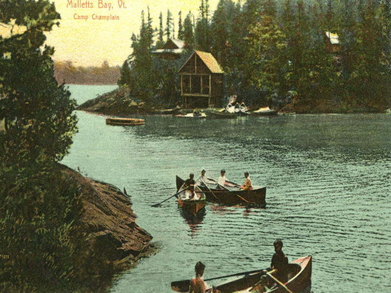 People canoing towards Camp Champlain